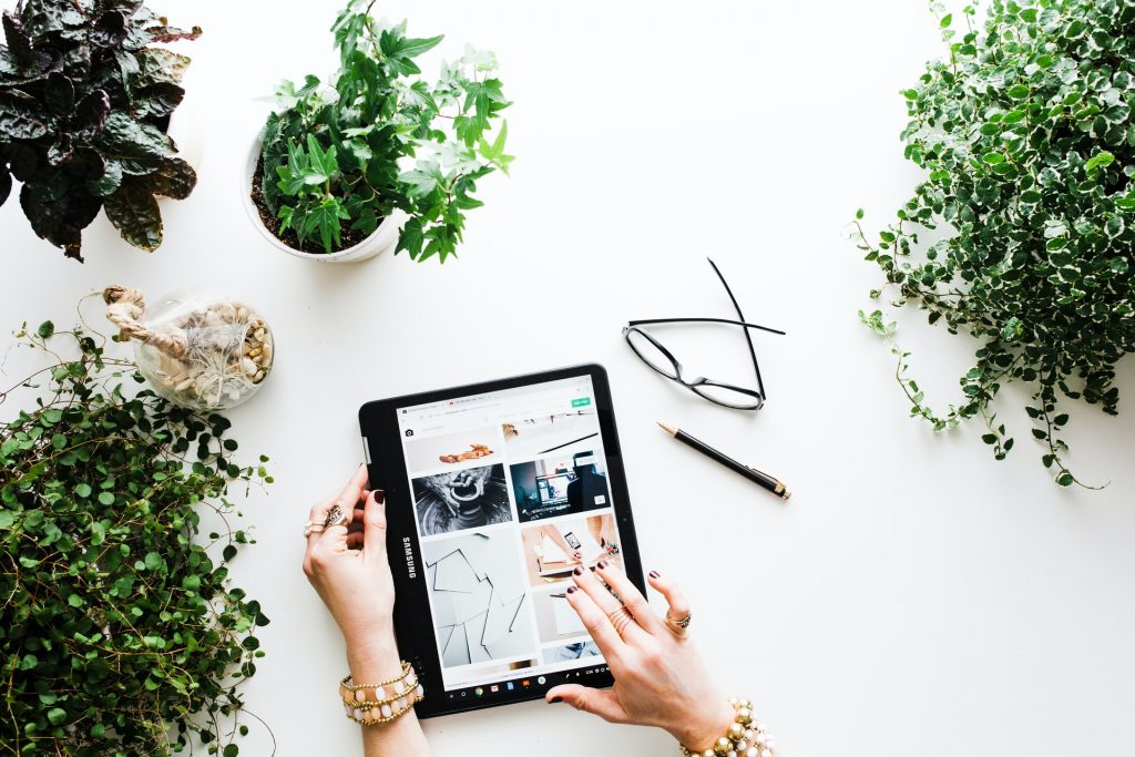 student entrepreneur on ipad surrounded by plants